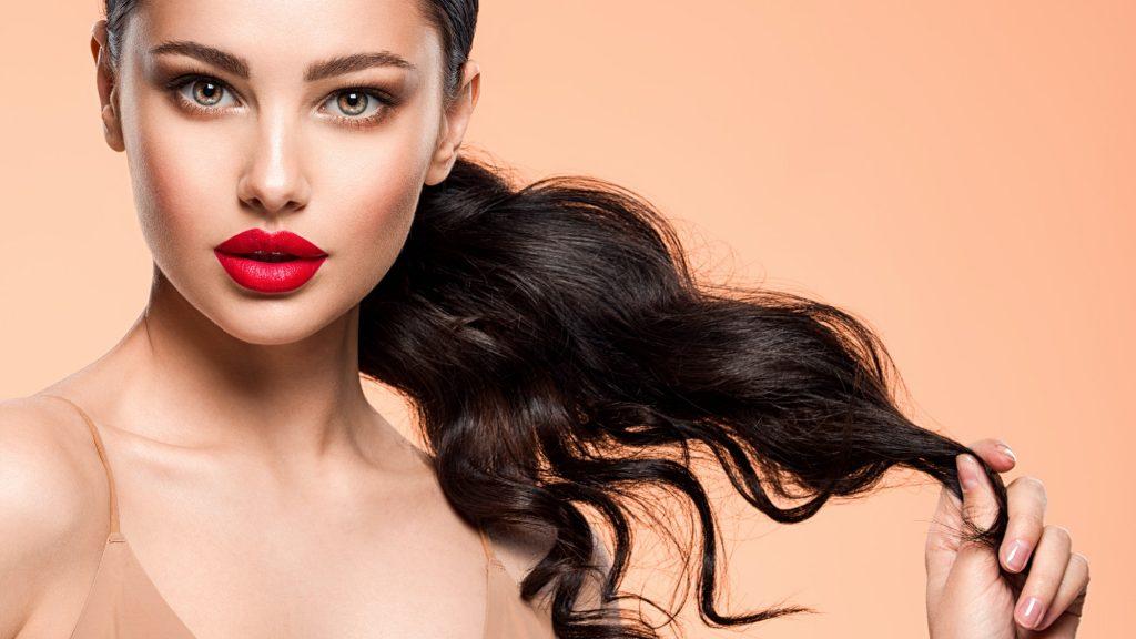 Hermosa chica con un lápiz labial rojo en los labios.