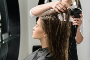 hairdresser drying hair of young woman in beauty salon